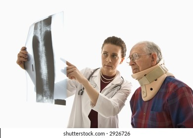 Mid-adult Caucasian female doctor ponting at x-ray with elderly Caucasian male in neck brace looks on.