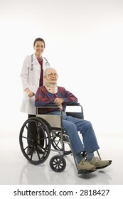 Mid-adult Caucasian female doctor pushing elderly Caucasian male with neck brace in wheelchair.