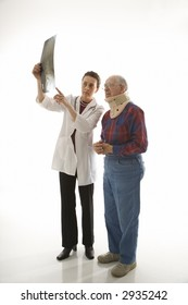 Mid-adult Caucasian female doctor showing x-ray to elderly Caucasian male in neck brace.