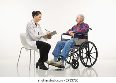 Mid-adult Caucasian female doctor taking notes with an elderly Caucasian male in wheelchair to her side.