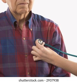 Mid-adult Caucasian female hand with stethoscope at elderly Caucasian male's chest.