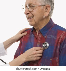 Mid-adult Caucasian female hands listening  to elderly Caucasian male's heart with stethoscope.