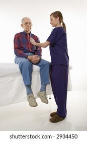 Mid-adult Caucasian female in scrubs listening to elderly Caucasian male's heart beat.