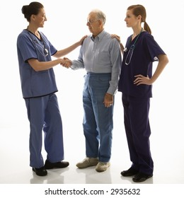 Mid-adult Caucasian female in scrubs shaking hand of elderly Caucasian male with another mid-adult Caucasian female with hand on his shoulder.