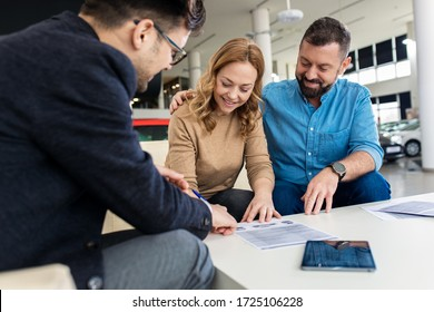 Mid-adult couple talking with sales agent and signing contract for new car in modern car showroom.