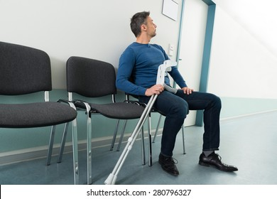 Mid-adult Man With Crutches Sitting On Chair In Hospital