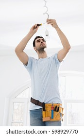 Mid-adult man fixing light bulb wiring in new house