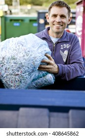 A mid-adult man recycling a bag of shredded paper