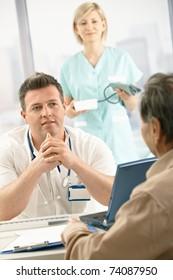 Mid-adult medical doctor talking to elderly patient, nurse holding blood pressure gauge in background.
