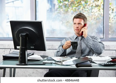 Mid-adult successful businessman calling on landline phone listening to conversation sitting at office desk with coffee mug in hand.