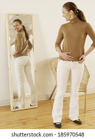 Mid-Adult Trying on Jeans in Mirror