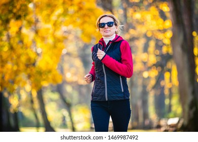 Mid-adult woman running in city park