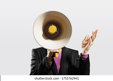 Mid-adult woman shouting through megaphone arms raised
