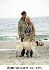 Mid-aged cople with dog on sea shore autumn