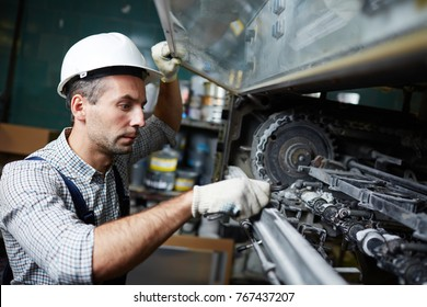 Mid-aged man in helmet, gloves and uniform repairing regulating system of factory machine