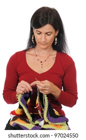A midaged woman with bavarian dirndl knitting with colorful wool