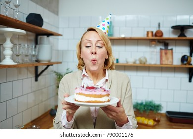 Mid-aged woman blowing burning candles on birthday cake in the kitchen