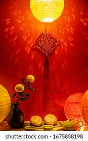 Mid-Autumn mooncakes and tea under colorful lantern lights in red background
