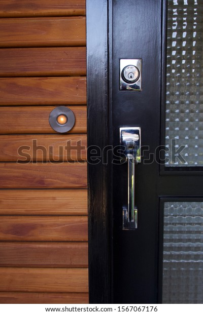 Mid-century modern black door with chrome handles and horizontal, cedar siding at a home's entry.