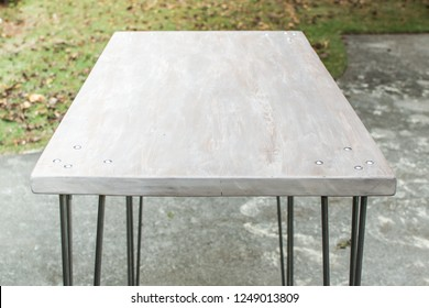 Midcentury modern handmade standing desk with a whitewashed wooden tabletop and steel hairpin legs. Outdoor setting. Table designed for indoor use.