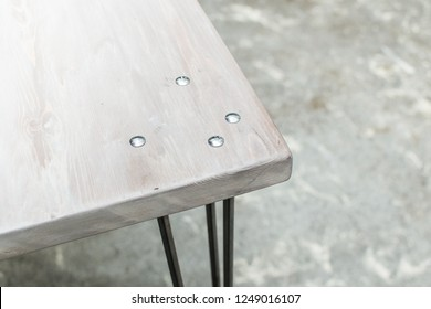 Midcentury modern handmade standing desk with a whitewashed wooden tabletop and steel hairpin legs. Outdoor setting. Table designed for indoor use. Higher angle, close up.