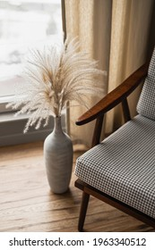 Mid-century retro chair and pampas grass bouquet in clay pot against window with curtains. Modern aesthetic minimalist home, living room interior design concept