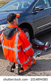 MIDDELBURG, NETHERLANDS - April 06, 2013: An auto mechanic of the road service in an orange uniform raises the car with a jack to repair the wheel