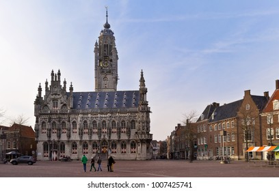 MIDDELBURG, NETHERLANDS - April 07, 2013: Tourists are walking along the central square of Middelburg near the Gothic City Hall 1458
