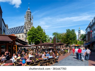 Middelburg, the Netherlands, August 16, 2015: City center with crowded terraces, town hall and church tower on a sunny day