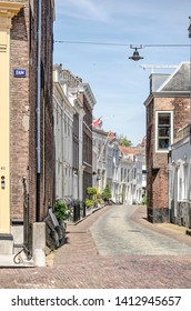 Middelburg, The Netherlands, May 30, 2019: street in the old town lined with two or three storey houses with brick or plaster facades on a sunny day
