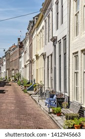 Middelburg, The Netherlands, May 30, 2019: row of facades of houses with brick facades and semi-private zones with plants, fences and benches