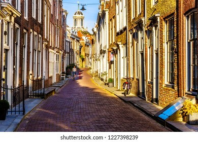 Middelburg / the Netherlands - Sept. 17, 2018: Dutch Biker under sunset in a Narrow Street in the Historic City of Middelburg in Zeeland Province, the Netherlands