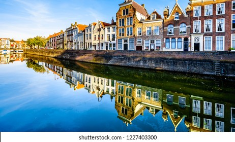 Middelburg / the Netherlands - Sept. 17, 2018: Sunset over a row of Houses that are reflecting on the water surface of a canal in the Historic City of Middelburg in Zeeland Province, the Netherlands
