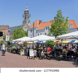 Middelburg, Zeeland, NLD - JUN 30, 2018 - Outdoor café at 'Beddewijkstraat', 'Schuiffelstraat' (street names). In the background the townhall.