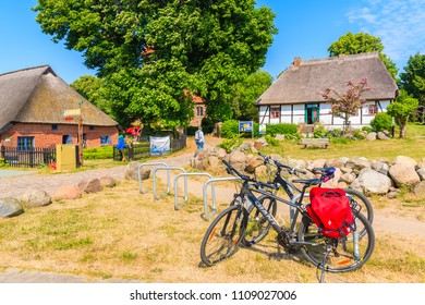 MIDDELHAGEN VILLAGE, RUEGEN ISLAND - MAY 31, 2018: Bicycle parking in Middelhagen village with traditional straw roof houses, Baltic Sea, Germany. Rugen is popular destination for cyclists in summer.