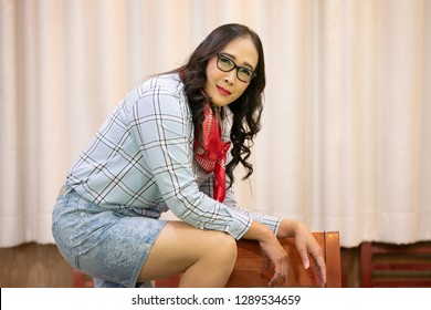 Middle adulthood long black hair Glasses woman wearing plaid shirt with cowboy bandana on Curtain background. attractive cowgirl in checkered shirt with blank space.