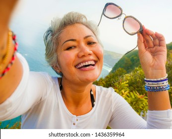 middle age 50s happy and cheerful Asian woman with grey hair taking selfie with mobile phone at beautiful tropical beach island smiling at cliff viewpoint enjoying Summer holidays travel destination