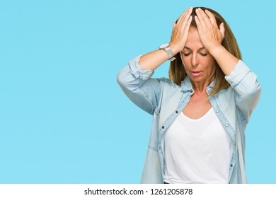 Middle age adult woman wearing casual denim shirt over isolated background suffering from headache desperate and stressed because pain and migraine. Hands on head.