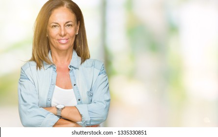 Middle age adult woman wearing casual denim shirt over isolated background happy face smiling with crossed arms looking at the camera. Positive person.