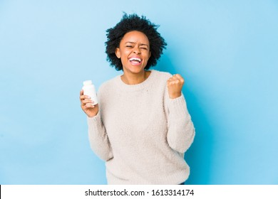 Middle age african american woman holding a vitamin bottle cheering carefree and excited. Victory concept.