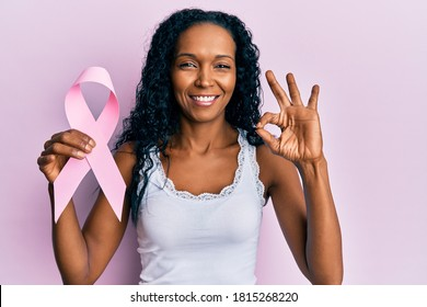 Middle age african american woman holding pink cancer ribbon doing ok sign with fingers, smiling friendly gesturing excellent symbol