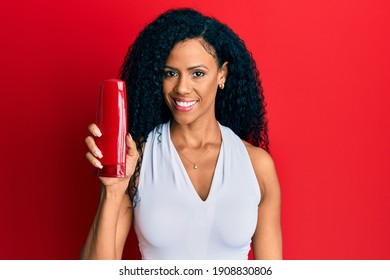 Middle age african american woman holding shampoo bottle looking positive and happy standing and smiling with a confident smile showing teeth
