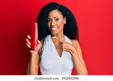 Middle age african american woman holding shampoo bottle smiling happy pointing with hand and finger