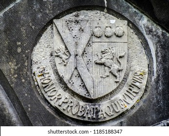 A middle age amblem on the stone. Honor probataque virtue; honor and virtue.