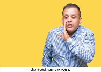 Middle age arab business man over isolated background hand on mouth telling secret rumor, whispering malicious talk conversation