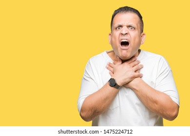 Middle age arab man wearig white t-shirt over isolated background shouting and suffocate because painful strangle. Health problem. Asphyxiate and suicide concept.