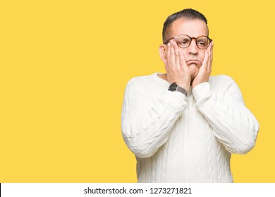 Middle age arab man wearing glasses over isolated background Tired hands covering face, depression and sadness, upset and irritated for problem
