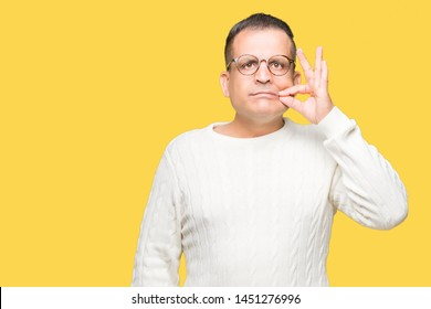 Middle age arab man wearing glasses over isolated background mouth and lips shut as zip with fingers. Secret and silent, taboo talking