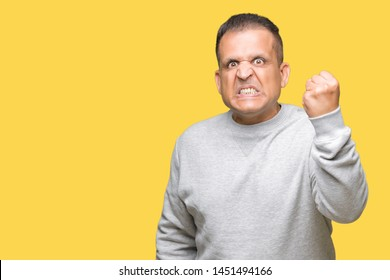 Middle age arab man wearing sport sweatshirt over isolated background angry and mad raising fist frustrated and furious while shouting with anger. Rage and aggressive concept.
