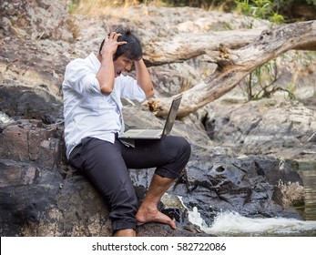 Middle age asian businessman in casual suit working in nature forest with crazy/mad/angry/stressed/serious feeling, working with laptop computer, business in forest/park/outdoor crazy feeling concept